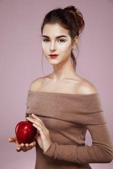 Mulher sorrindo segurando maçã vermelha rosa