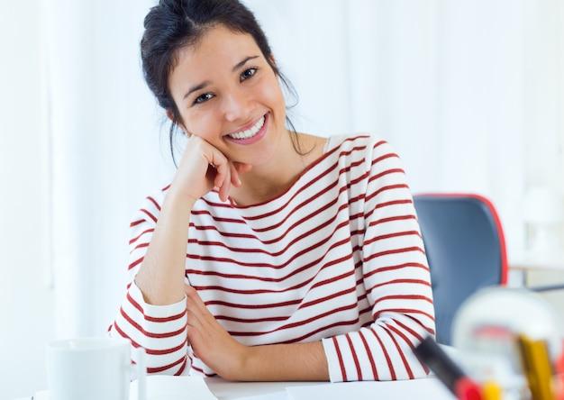 Mulher sorrindo sentado à mesa