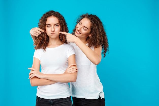 Mulher sorrindo, tocando as bochechas dela irmã gêmea sobre azul.