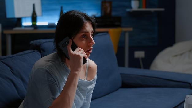 Mulher sozinha chocada recebendo notícias trágicas caindo smartphone