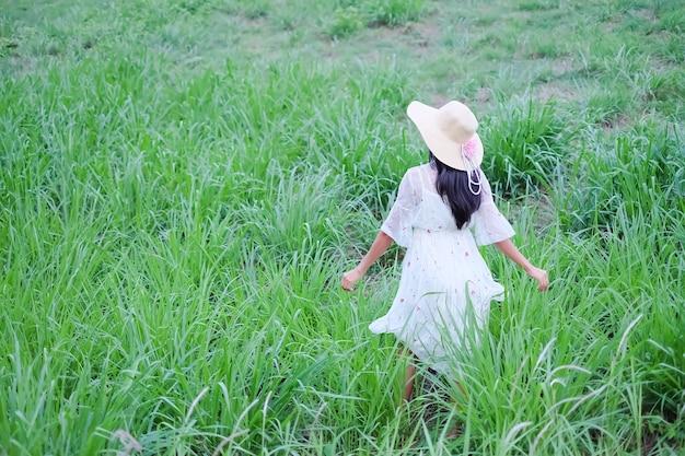 Mulher sozinha com chapéu e vestido branco andando no parque de grama verde. espaço livre. férias de verão tropical de natureza turística. estilo de vida feliz. coração partido ou amor conceito de dia dos namorados.