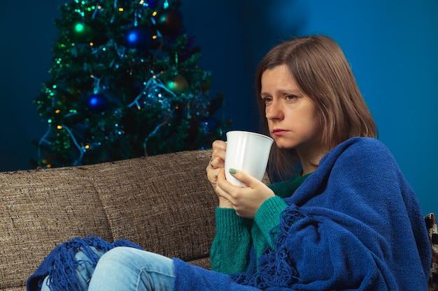 Mulher sozinha com um copo de uma bebida quente no sofá na véspera de natal como ficar em casa para salvar vidas