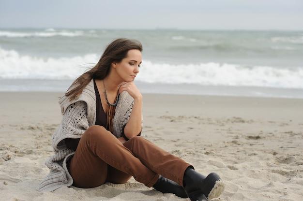 Mulher sozinha e triste sentada em uma praia de mar
