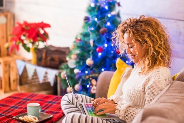 Mulher sozinha em casa no dia de natal está usando seu laptop assistindo filmes ou comprando alguma coisa - sentada no sofá com biscoitos e chá ou café - árvore de natal no fundo