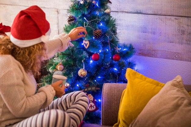 Mulher sozinha em casa no dia de natal tocando e fazendo a árvore de natal com uma xícara de chá ou café na mão