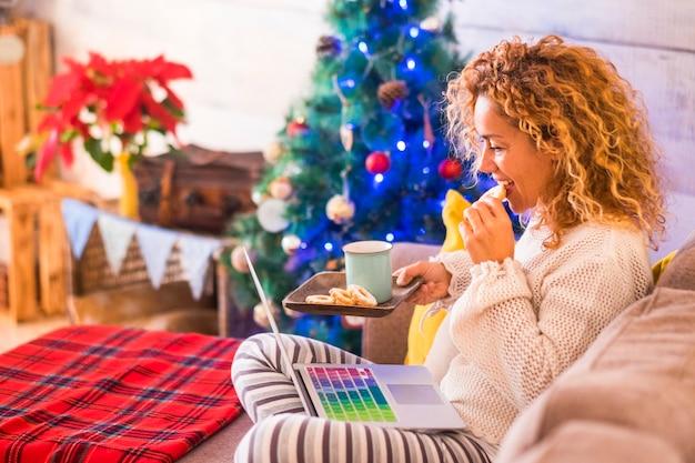 Mulher sozinha em casa no sofá comendo biscoitos e assistindo filmes ou séries com seu laptop - dia de natal tomando chá ou café e relaxada
