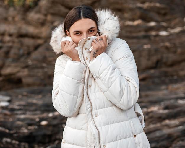 Mulher sozinha na praia com casaco de inverno