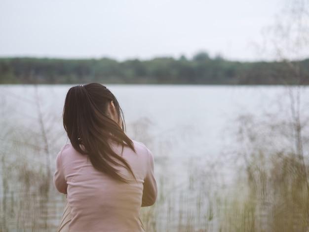 Mulher sozinha sentada sozinha ao lado do rio. conceito solitário.