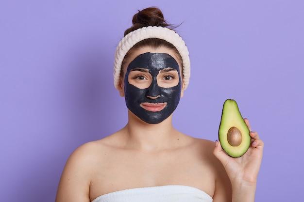 Mulher spa com máscara facial e metade de abacate nas mãos