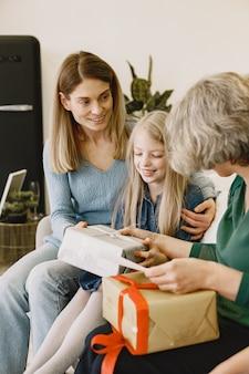 Mulher, sua mãe e sua filha sentadas em um sofá. menina guarda uma caixa com presente.
