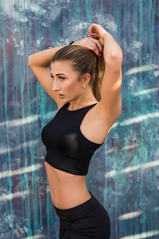Mulher suada de fitness, respirando na corrida matinal. atleta feminina em repouso, treino ao ar livre ao ar livre, corrida em pausa, vestindo roupa esportiva, em pé perto da parede de concreto