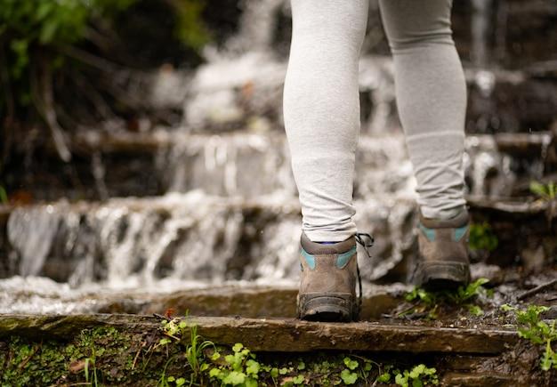 Mulher subindo em uma cachoeira usando calças e botas cinza