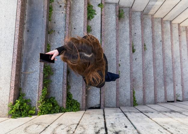 Mulher subindo escadas e usando smartphone