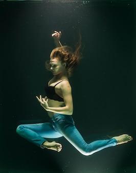 Mulher submersa que levanta em calças de brim