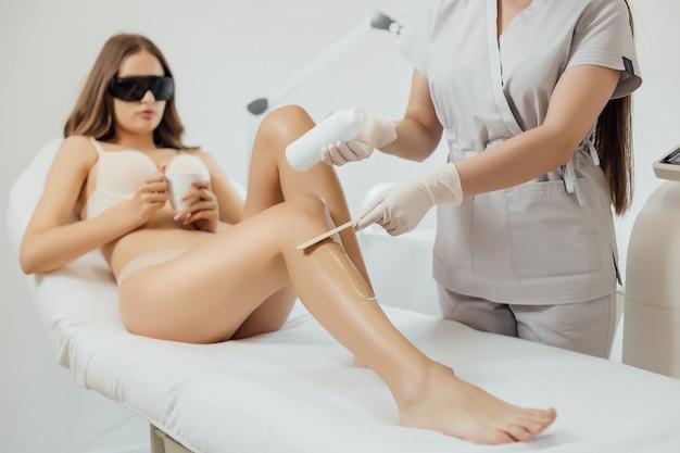 Mulher submetida a um procedimento de depilação a laser e cosmetologia