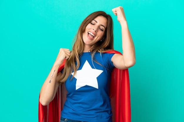 Mulher super-heroína caucasiana isolada em um fundo azul comemorando uma vitória