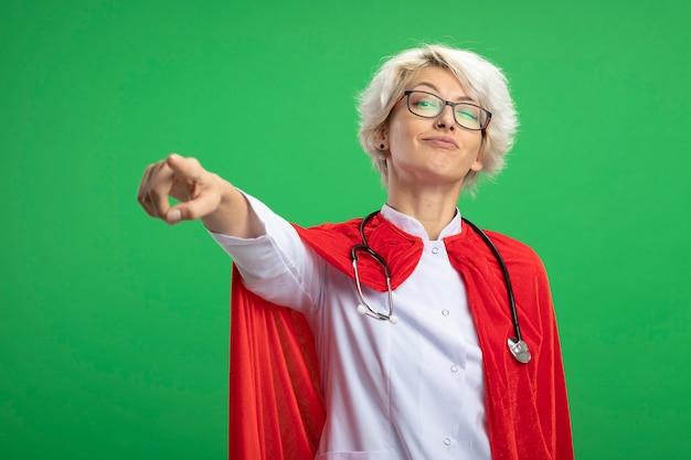 Mulher super-heroína eslava satisfeita em uniforme de médico com capa vermelha e estetoscópio em óculos ópticos