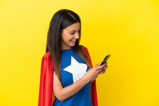 Mulher super-heroína isolada em fundo amarelo enviando uma mensagem ou e-mail com o celular