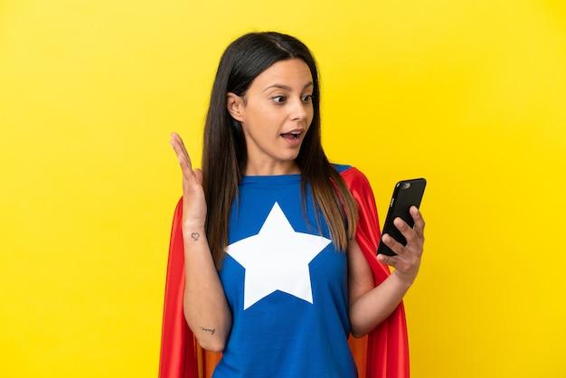 Mulher super-heroína isolada em fundo amarelo olhando para a câmera enquanto usa o celular com expressão de surpresa