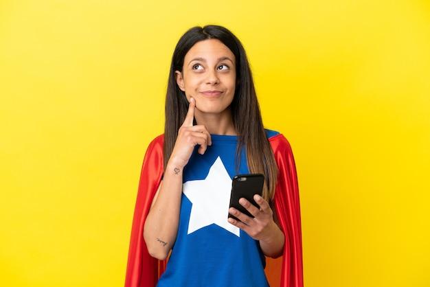 Mulher super-heroína isolada em fundo amarelo usando telefone celular e pensando