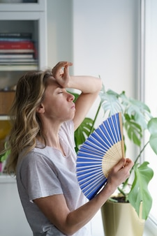 Mulher superaquecida em uma camiseta usando ventoinha de ondas sofre de suor de calor, se esfria, sente-se lenta