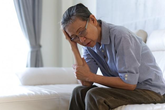 Mulher superior asiática madura que senta e que tem uma dor de cabeça.