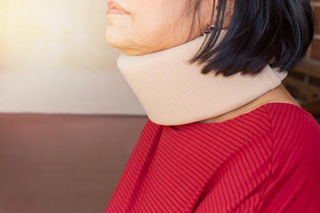 Mulher superior asiática que veste o colar cervical para ferimento do pescoço.