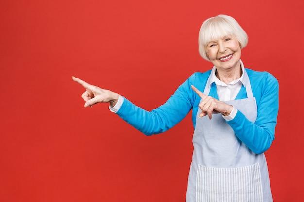 Mulher superior na posição do avental isolada no fundo vermelho. ela é uma boa dona de casa. ela gosta de cozinhar comida saborosa.