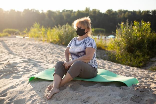 Mulher superior que desgasta a máscara médica na natureza nas areias. conceito de coronavírus. proteção respiratória