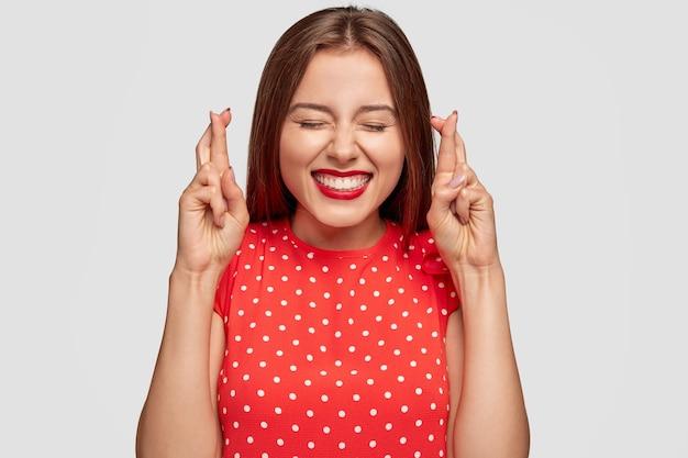 Mulher supersticiosa com batom vermelho posando contra a parede branca