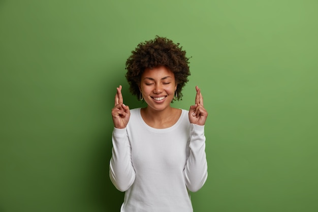 Mulher supersticiosa e esperançosa com penteado afro, sorri amplamente, cruza os dedos para que os sonhos se tornem realidade, faz desejos e tem fé em uma vida melhor, usa blusão branco, isolada na parede verde