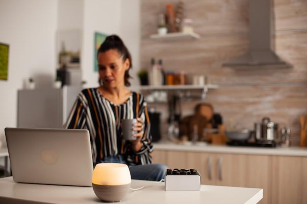 Mulher surfando no laptop e difusor com óleos essenciais