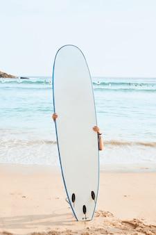 Mulher surfista esconder atrás de prancha de surf branca na praia