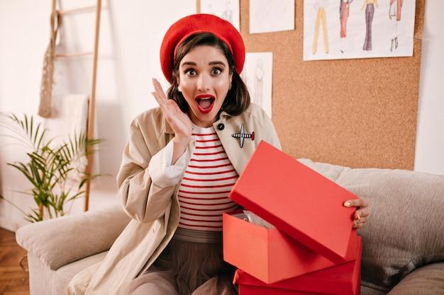 Mulher surpreendida abre a caixa de presente e olha para a câmera. garota maravilhosa chocada em roupas de outono modernas se alegra com seu presente.