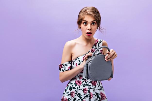 Mulher surpreendida abre sua bolsa estilosa. linda garota com vestido de verão floral detém bolsa cinza em pano de fundo isolado.