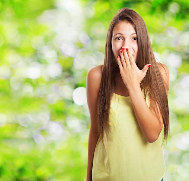 Mulher surpreendida cobrindo a boca com a mão