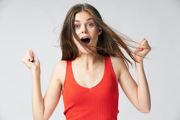 Mulher surpreendida com a boca aberta segurando as mãos na frente de sua camiseta vermelha