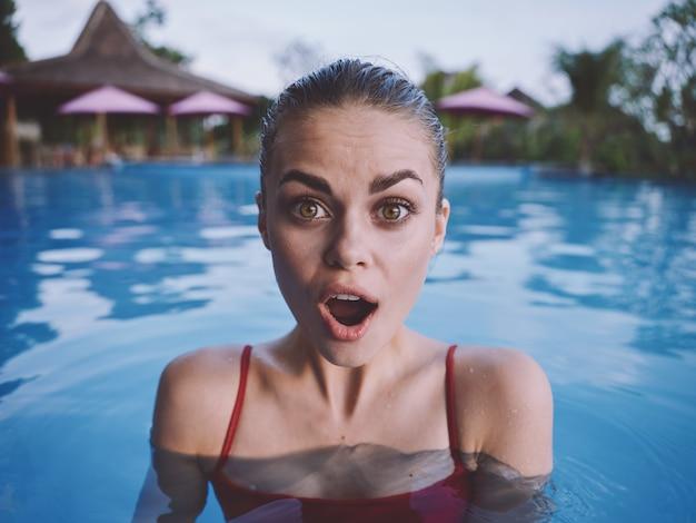 Mulher surpreendida com a boca bem aberta nadando na piscina com um maiô vermelho vista recortada