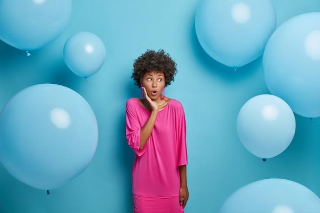 Mulher surpreendida com cabelo afro, vestida com vestido rosa festivo, olha em choque à direita, ergue-se
