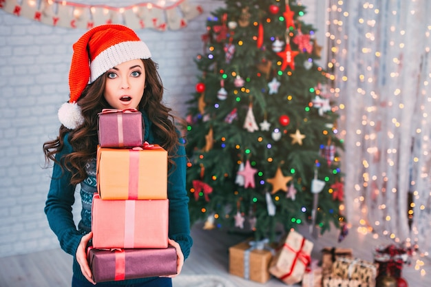 Mulher surpreendida com presentes e árvore de natal. liquidação de natal.