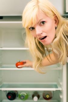 Mulher surpreendida com uma geladeira vazia