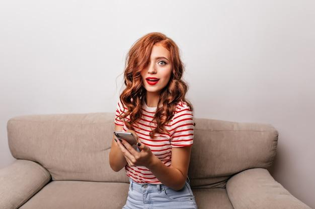 Mulher surpreendida de olhos azuis com lábios vermelhos, sentada no sofá. garota ruiva encantadora com telefone, posando no quarto dela, no sofá.