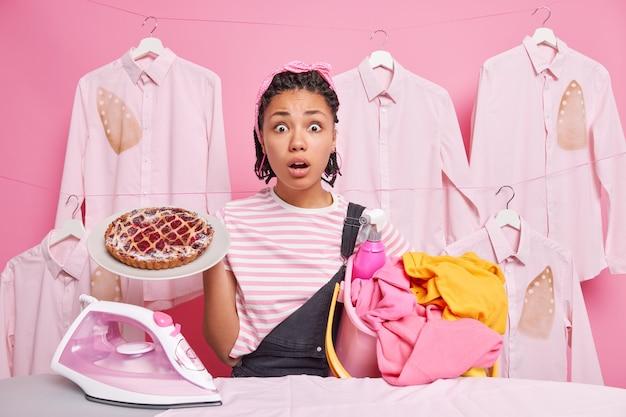 Mulher surpreendida, de pele escura, trabalhadora e olhando para a câmera enquanto lava a roupa e cozinha segurando uma deliciosa cesta de torta indo passar a ferro ocupada com responsabilidades domésticas vestida casualmente