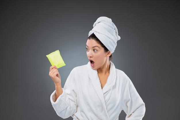 Mulher surpreendida de roupão e toalha enrolada na cabeça segurando um absorvente higiênico para a menstruação
