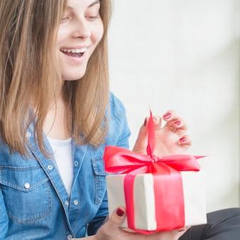 Mulher surpreendida, desembrulhando a caixa de presente de aniversário