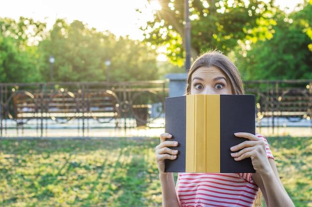 Mulher surpreendida e chocada no parque com um livro.