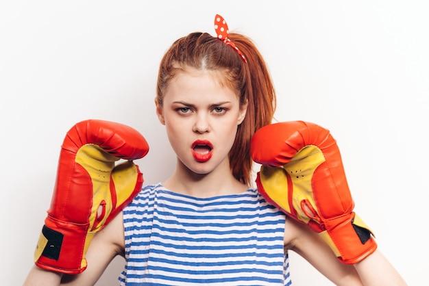 Mulher surpreendida em luvas de boxe em uma camiseta listrada de fundo claro penteado maquiagem