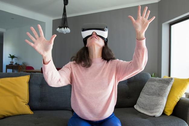 Mulher surpreendida em óculos de realidade virtual, gesticulando as mãos