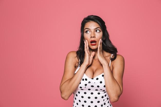 Mulher surpreendida em trajes de banho posando isolada sobre uma parede rosa, olhando de lado com a boca aberta.