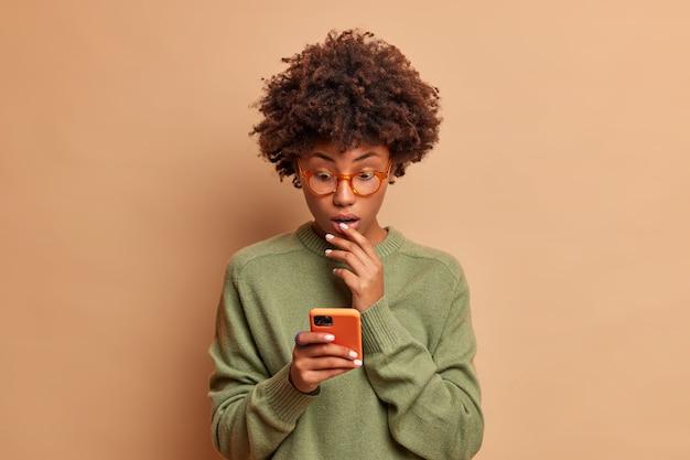 Mulher surpreendida encara a tela do smartphone, verifica a caixa de e-mail, lê feed de notícias e mantém a boca aberta de maravilha, vestida com um macacão casual isolado na parede marrom